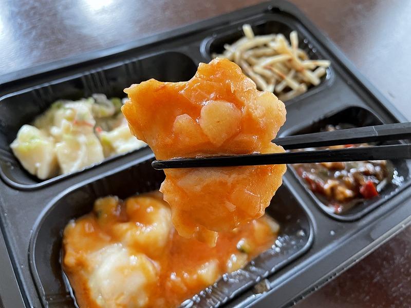 まごころケア食のズッキーニとチキンのトマト煮弁当に入っているチキンのトマト煮を箸で持ち上げているアップ画像