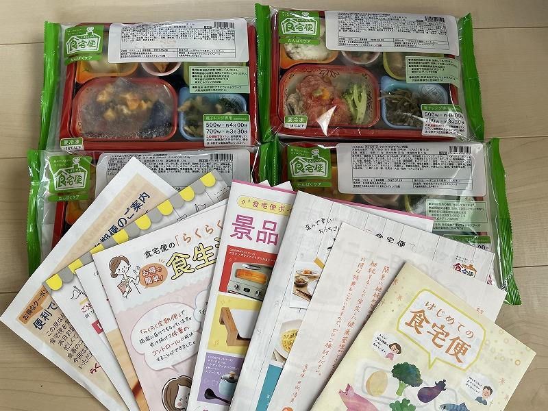 食宅便のお試しセットに同梱されている4個のお弁当と冊子類。